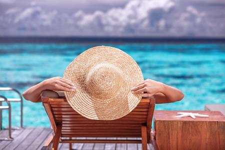 Luxus weiblichen Bräunen am Strand, die mit großen stilvollen Hut, genießen Sie einen wunderschönen Meerblick, Sommer Reise-und Tourismus-Konzept