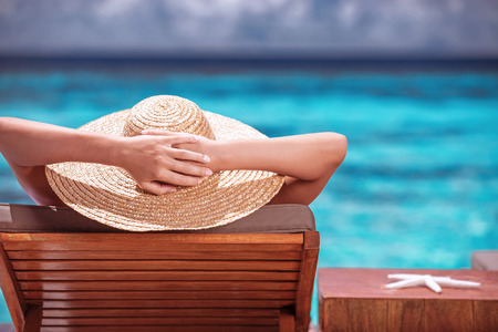 Luxury female tanning on the beach, wearing big stylish hat, enjoying beautiful seascape, summer fashion, travel and tourism concept photo