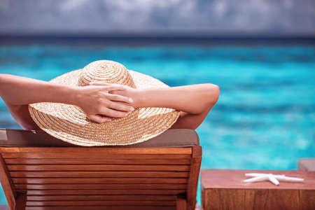 Luxury female tanning on the beach, wearing big stylish hat, enjoying beautiful seascape, summer fashion, travel and tourism concept photo