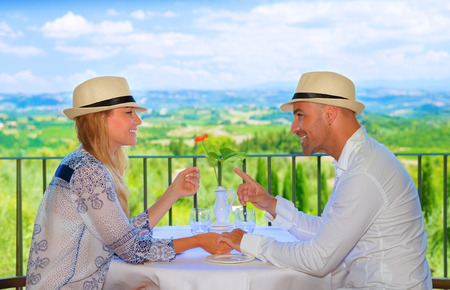 Young couple having breakfast on the terrace in restaurant, Europe, Italy, Tuscany, wonderful view, summer travel and tourism concept photo
