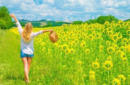 Glückliche Frau, die auf Sonnenblumenfeld im sonnigen Tag, Hände, schöne Landschaft, europäische Natur, Landwirtschaft Konzept auferweckt Standard-Bild