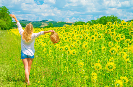 Happy woman walking on sunflower field in sunny day, raised up hands, beautiful landscape, European nature, farming concept photo