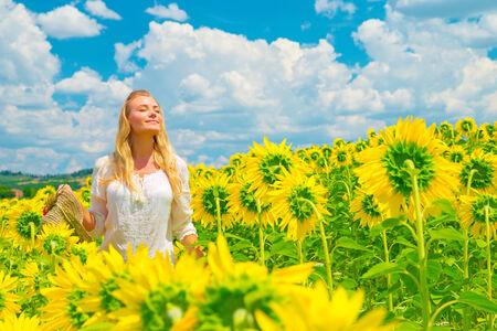 Hermosa mujer con los ojos cerrados de placer de pie en los campos de girasoles amarillos frescos, magnífico paisaje pintoresco