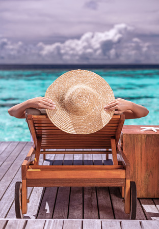 Woman on luxury beach resort, female tanning on sunbed, female wearing a big stylish hat, young girl enjoying beautiful seascape, relaxation on summer travel,  tourism concept photo