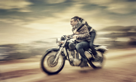 people in the street: Two happy people riding on motorcycle, slow motion effect, grunge style photo, romantic relationship, speed and adventure concept