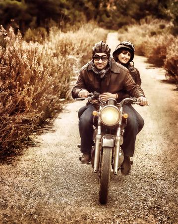 casco moto: Imagen de estilo vintage de dos ciclistas felices cabalgando sobre la carretera, familia activa disfrutando trayecto en transporte lujo extremo, el concepto libertad Foto de archivo