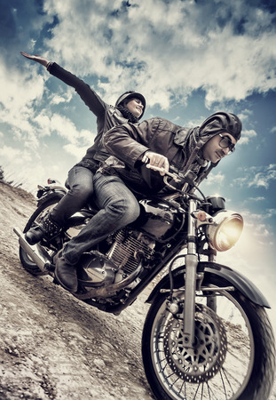 Active couple on motorcycle, happy woman riding with raised up hands with pleasure, enjoying speed, family in motorbike tour, grunge style photo