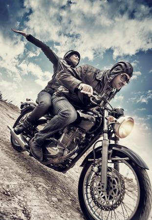 Aktive Paar auf dem Motorrad, glückliche Frau Reiten mit bis erhobenen Händen mit Vergnügen, genießen Geschwindigkeit, Familie im Motorrad-Tour, Grunge-Stil Foto