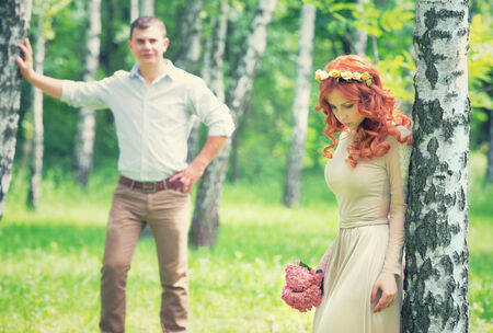 Romantic gentle bride posing near birch tree, handsome groom looking on her, beautiful young loving couple, happy wedding day concept photo