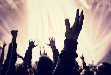 Grunge style photo of silhouette of people hands raised up on musical concert, enjoying music, dance club, active night life concept photo