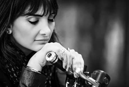 Closeup portrait of beautiful biker woman with closed eyes resting on steering wheel, black and white photo, active lifestyle concept photo