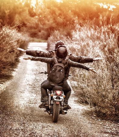 libertad: Imagen de estilo vintage, vista posterior de dos ciclistas felices cabalgando sobre la carretera con las manos levantadas hacia arriba, familia activa que disfruta de viaje en transporte lujo extremo, concepto de libertad Foto de archivo