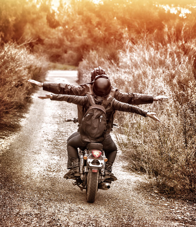 freedom girl: Vintage style image, rear view of two happy bikers riding on the road with raised up hands, active family enjoying journey on luxury extreme transport, freedom concept