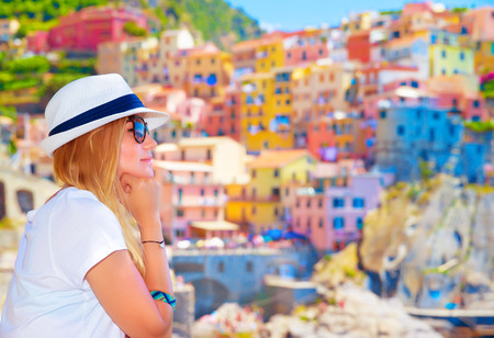 Traveler girl enjoying colorful cityscape, spending summer vacation in Europe, Italy, Cinque Terre, beautiful painted buildings photo
