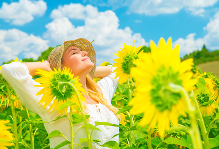 italian village: Portrait of cute girl with closed eyes enjoying sunny day and  beautiful yellow sunflowers field, spending time in countryside, pleasure and freedom concept Stock Photo