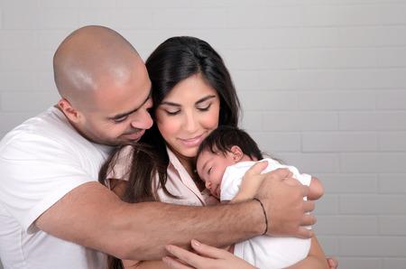 papa y mama: Retrato de familia feliz árabe en casa, los padres jóvenes que tienen en las manos poco bebé recién nacido, el amor y la felicidad concepto dulce Foto de archivo