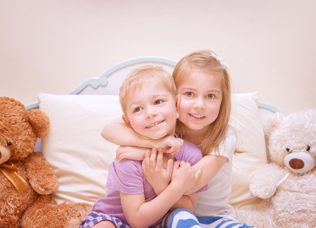 Portrait of two cute kids having fun at home, brother and sister playing in bedroom, healthy lifestyle, family love concept photo