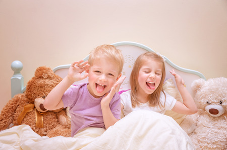 Happy kids make faces, cute brother and sister make grimace, having fun at home, lovely family, active childhood concept photo