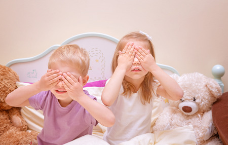 hide and seek: Little brother and sister play in hide and seek at home, covered eyes with hands, having fun together, family relationship, happy childhood concept