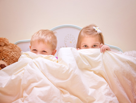 Two joyful kids playing game in bedroom, siblings sitting on the bed and covered with blanket, hide and seek, happy childhood concept photo