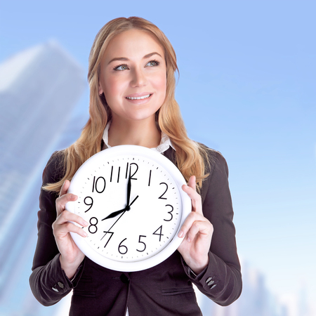 vp: Portrait of happy smiling business woman holding in hands big clock outdoors, come to work on regular schedule, success concept