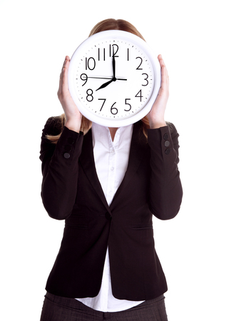 punctual: Business woman wearing formal suit and holding big clock on face, isolated on white background, punctual worker concept