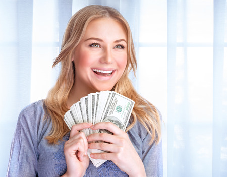 woman holding money: Portrait of happy excited woman holding in hands lot of money, at home, financial success, wealth concept Stock Photo