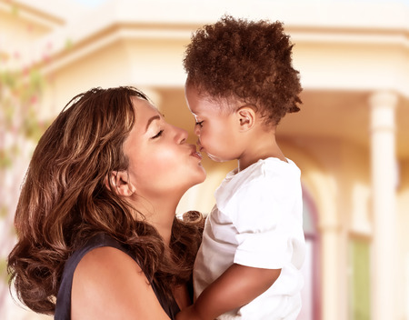 Side view of cheerful mother holding on hands cute little curly son and kiss him, spending time outdoors near great beautiful house, happy African family photo