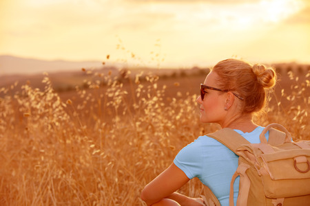 Beautiful traveler girl enjoying golden wheat field in sunset light, beautiful summer nature, farmland in Europe, travel and tourism concept  photo