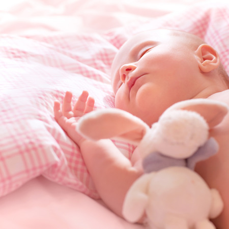 Newborn baby sleeps, relaxing in the bed, adorable healthy child dreaming, safe childhood concept  photo