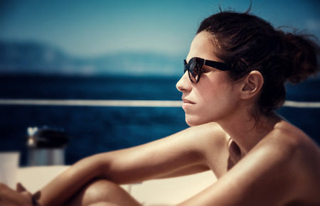 Closeup portrait of attractive female sitting on the yacht deck and enjoying warm sunny day, fashionable look, side view, sea cruise, traveling on luxury water transport  photo