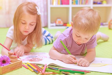 preschool classroom: Happy baby boy & girl enjoying homework, preschool developing drawing skills, talented children learning art, kids back to school concept Stock Photo