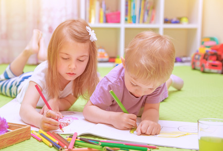 Happy baby boy & girl enjoying homework, preschool developing drawing skills, talented children learning art, kids back to school concept Stock Photo