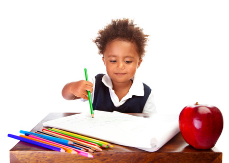 kid school: Portrait of cute little African schoolboy sitting behind desk and painting with colorful pencil, having for lunch big red apple, happy pupil concept