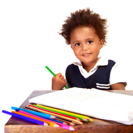 Portrait of adorable sweet little black boy drawing using many colorful pencil, isolated on white background, back to school concept