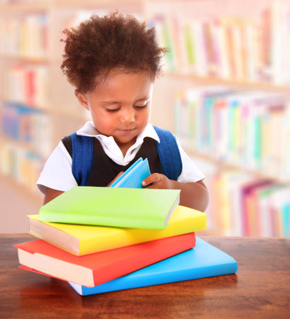 Little clever preschooler in the library, reading books, cute African boy preparing to go to first class, enjoying study, elementary school concept