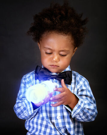 inventing: Portrait of cute little African schoolboy holding in hands bright lamp, isolated on black background, innovation and inventing, little scientist concept Stock Photo