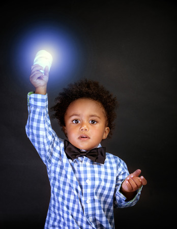 Little genius with illuminated lamp in hand isolated on black background, african boy is a great physics, back to school concept photo