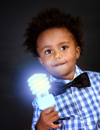 bright idea: Little genius with illuminated lamp in hand isolated on black background, african boy is a great physics, back to school concept
