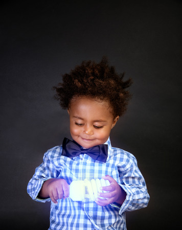 Portrait of cute little African schoolboy holding in hands bright lamp, isolated on black background, innovation and inventing, little scientist concept Фото со стока