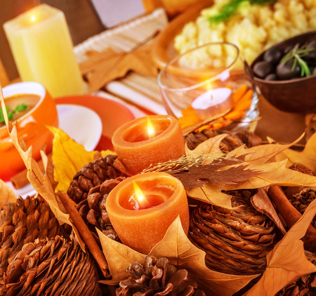 candle light table setting: Closeup photo on beautiful autumnal still life for Thanksgiving day, pine cone and dry leaves decoration for festive dinner