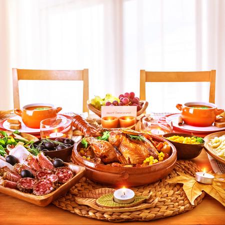Acción de Gracias cena día, sabroso pollo al horno en la pieza central de la mesa de fiesta, embutidos, luz de velas, tarjetas de felicitación, feliz celebración de las fiestas
