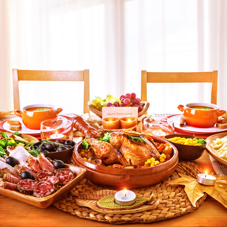 Thanksgiving day dinner, tasty baked chicken on centerpiece of festive table, cold cuts, candle light, greeting card, happy holiday celebration