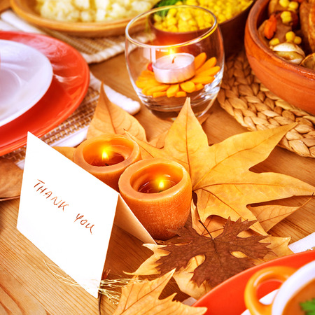 table decorations: Thanksgiving day, post card on festive table with text, thank you, holiday dinner, candle light, beautiful decoration, happy celebration concept