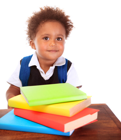 Portrait of cute little boy wearing school uniform with many colorful books isolated on white  photo