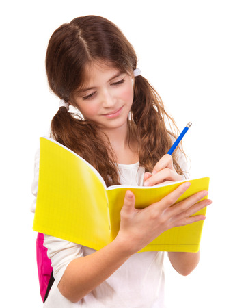 School girl writing in notebook isolated on white background photo