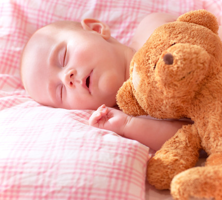 Portrait of adorable newborn baby sleeping on cute pink pillow with soft toy of teddy bear, day dreaming, love and childcare concept  photo