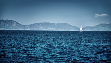 yacht race: Beautiful seascape, dark blue sea on high mountains background, luxury yacht floating in the distance, summer vacation concept