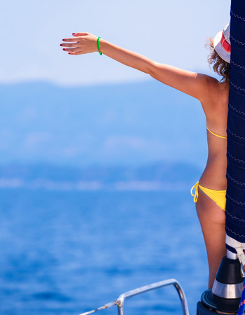 back up: Happy woman on sailboat, back side of cheerful girl with raised up hand enjoying majestic seaview, summer vacation concept