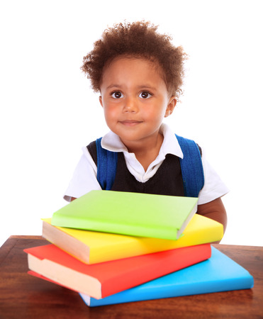 Portrait of cute little boy wearing school uniform with many colorful books isolated on white background, doing homework, back to school concept photo